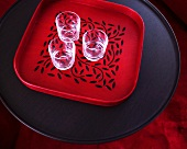 Three glasses on red tray on black table
