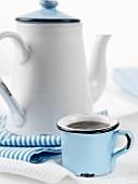 A mug of coffee and a coffee pot