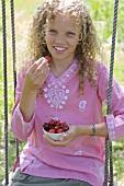 Girl sitting on a swing, eating cherries