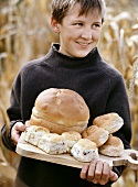 Boy holding bread and bread rolls on wooden board