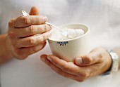 Hands holding a sugar bowl containing sugar cubes