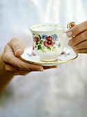 Hands holding a cup and saucer