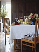 Wine, grapes, flowers and apples on laid table