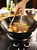 Cooking soba noodles and vegetables in a wok