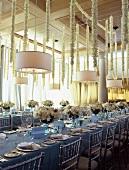 Festlich gedeckte Hochzeitstafel in Saal mit weisser Blumendeko auf Tisch & an Saaldecke