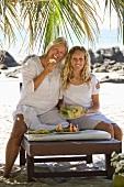 Mutter und Tochter essen Ananas am Strand