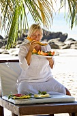Blond woman eating papaya on the beach