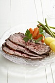 Three slices of roast beef with vegetables