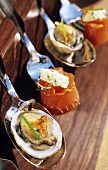 Oyster and salmon appetisers on spoons and forks