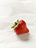 A strawberry on parchment paper