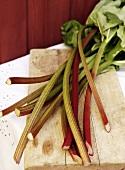 Sticks of rhubarb on wooden board