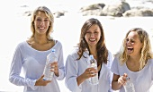 Three girls with bottles of water on the beach
