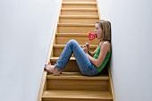 Mädchen mit Lutscher sitzt auf der Treppe