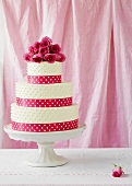 A wedding cake with red roses