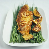 Trout with pine nuts and lemon wedges on chives