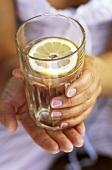 Hände halten ein Glas Wasser mit Zitronenscheibe