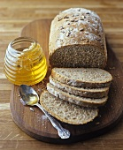 Jar of honey & loaf of wholemeal bread with sunflower seeds