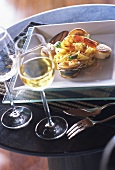 Linguine with seafood on plate and a glass of wine
