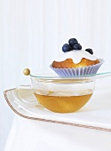 A blueberry muffin on a cup of tea