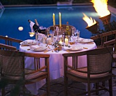 Table laid for special occasion by pool, evening atmosphere