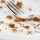 A cake fork surrounded by cake crumbs
