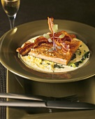 Salmon with fried bacon and herbs on creamed savoy cabbage