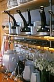 Saucepans, glasses and crockery on kitchen shelves