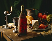 Still life with red wine, cheese, fruit and white bread