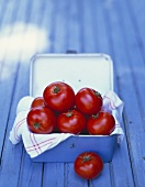 Tomatoes and tea towel in a metal box