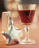A glass of red wine with a Christmas decoration