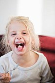 Blond girl with yoghurt on her tongue