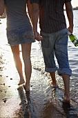 Junges Pärchen am Strand mit Sektflasche & -gläsern
