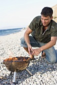 Young man kneeling in front of burning barbecue on beach