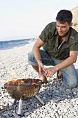 Junger Mann kniet vor brennendem Grill am Strand