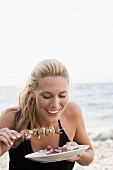 Blond woman eating shashlik
