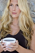 Blond woman holding a cup of tea