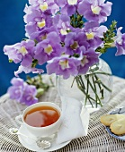 A cup of tea, biscuits and flowers