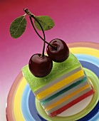 A colourful layer cake topped with two cherries