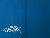 Fischgräte auf blauen Holzuntergrund gemahlt