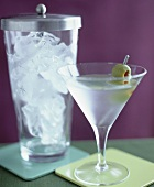 Martini with olive and a jar of ice cubes