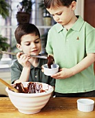 Two boys putting chocolate cake mixture into ramekins
