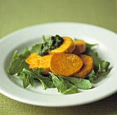 Roasted sweet potato slices with pesto on rocket salad