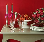 Tableware, nectarines, wine and candles on table