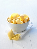 Raw pasta shells in a small bowl