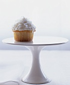 A coconut cupcake on a cake stand