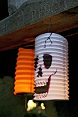 Two lanterns hanging up for Halloween