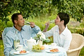 Young couple having champagne breakfast in garden