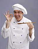 Cheerful chef with wooden spoon in his hand