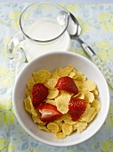 Cornflakes with milk and strawberry for breakfast
