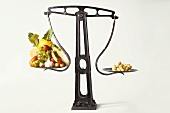 Picture symbolising diet: vegetables and peanuts on scales